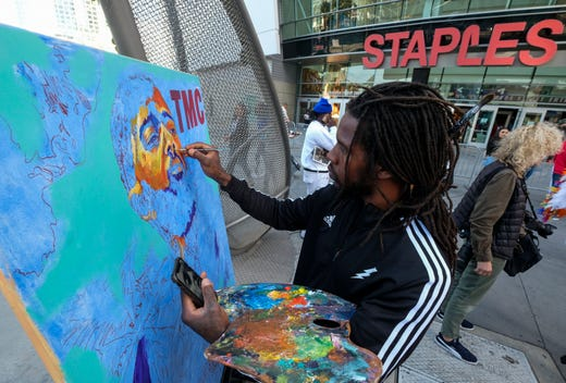 Artist Gift Davis works on a portrait of rapper Nipsey Hussle as fans wait in line to attend a public memorial at Staples Center in Los Angeles.