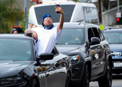 A driver takes a selfie as the funeral procession for Nipsey Hussle stops while driving through Los Angeles.
