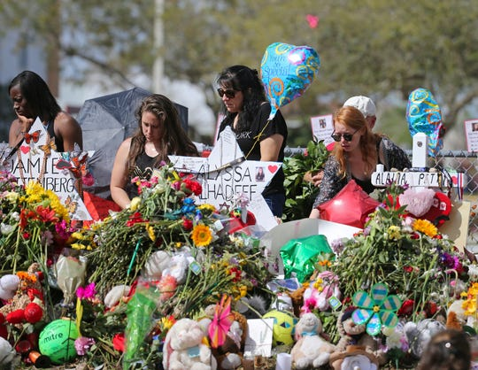 Mourners bring flowers on Feb. 25, 2018, as they pay tribute at a memorial for the victims of the shooting at Marjory Stoneman Douglas High School, in Parkland, Fla.