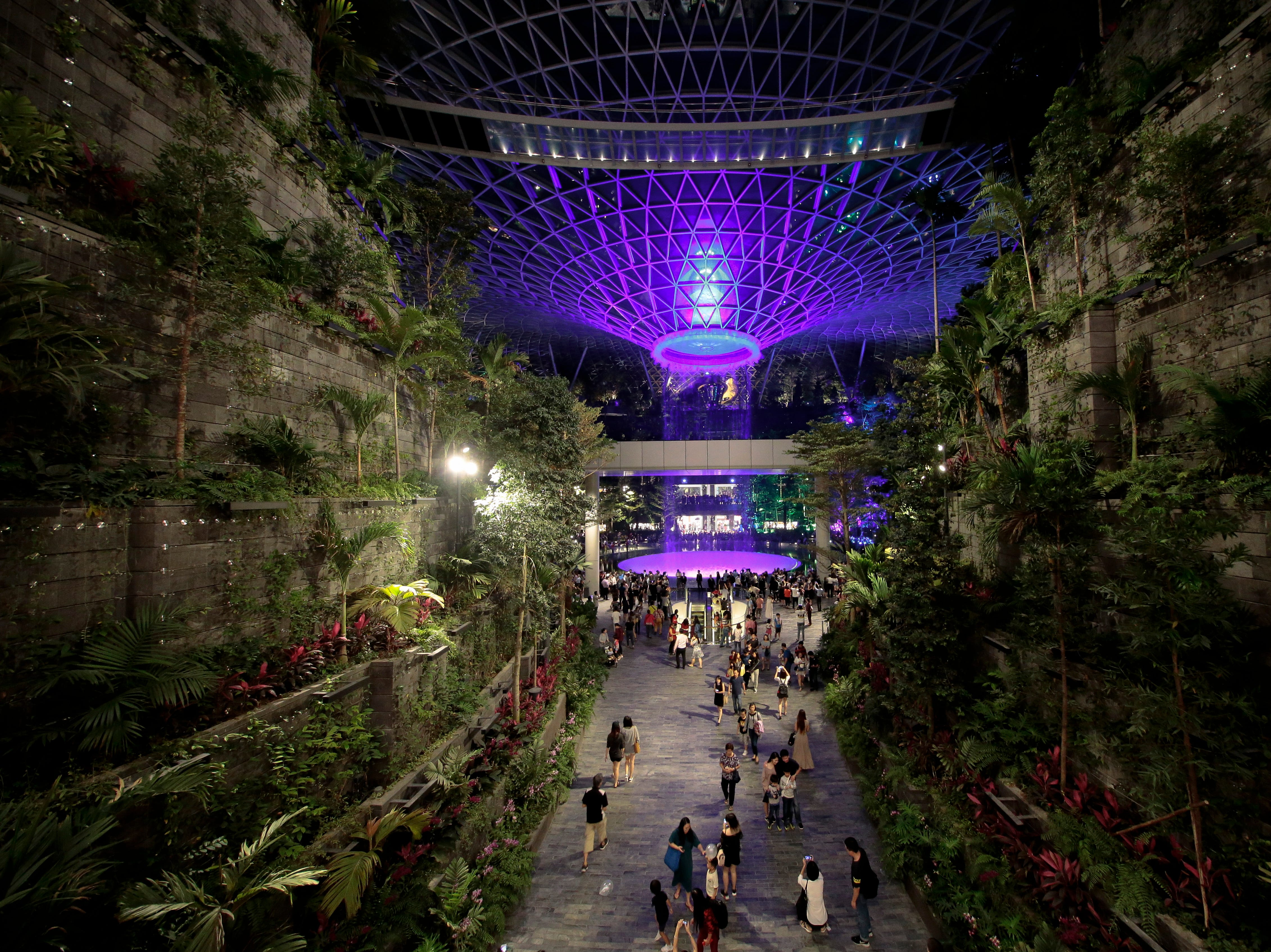 The Rain Vortex is pictured between greenery on the Forest Valley as a tram passes by inside Jewel Changi in Singapore on April 11, 2019.