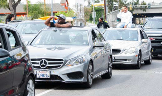 Vehicles in a funeral procession for Nipsey Hussle move slowly through Los Angeles after a memorial services at the Staples Center.