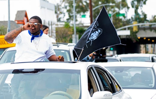 Vehicles in a funeral procession for Nipsey Hussle move slowly through Los Angeles after memorial services at the Staples Center.