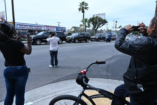 People gather to watch and shoot video of Nipsey Hussle's funeral procession following a memorial service at the Staples Center in Los Angeles.