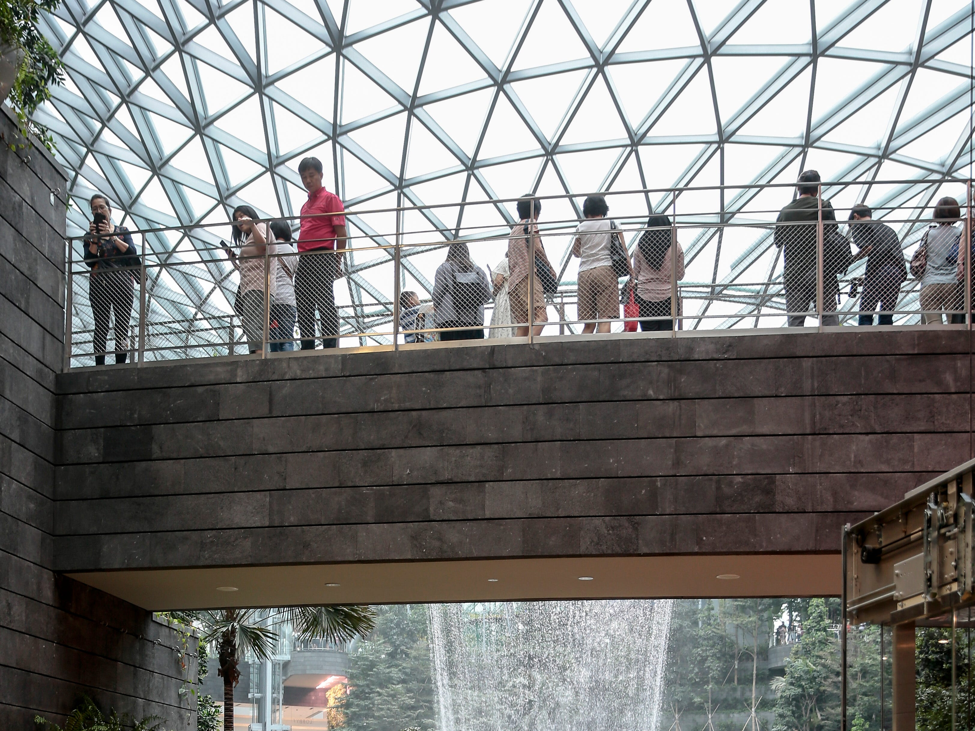 Members of the public are seen on corridors pictured against the Rain Vortex inside Jewel Changi in Singapore.