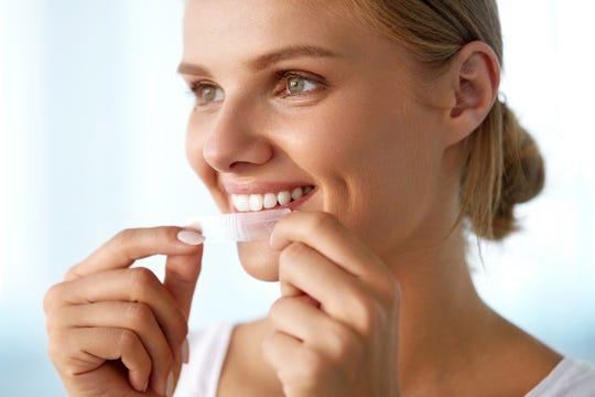 A woman prepares to put on a teeth whitening strip.