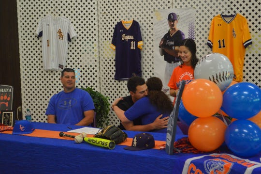 Alexandria Senior High's Colby Bordelon receives a hug from his mom after signing with Louisiana College Tuesday.