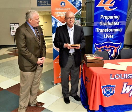 Mike Tudor (right) presents a Bible once belonging to Rebecca Beall to Louisiana College President Rick Brewer.