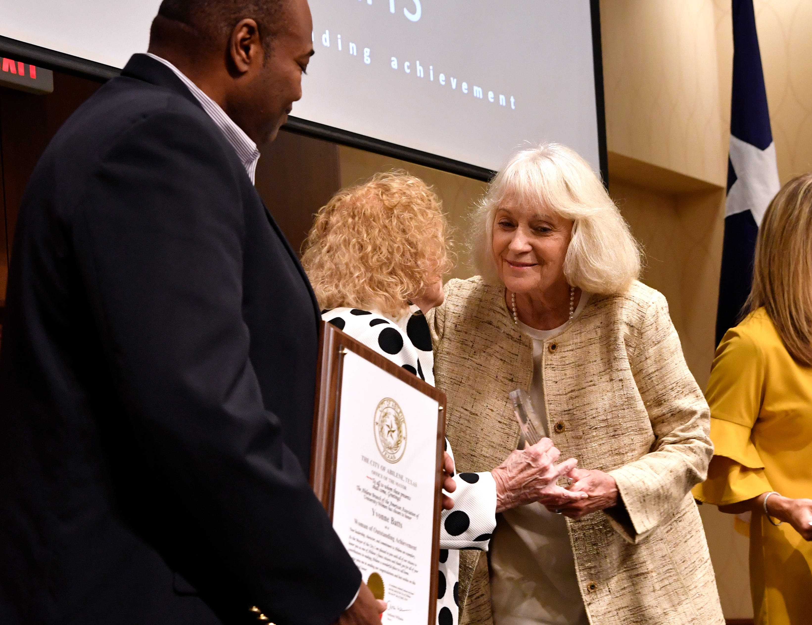 Yvonne Batts greets Martha Kiel onstage as Abilene Mayor Anthony Williams holds the plaque honoring her at Monday's 10th annual Women of Outstanding Achievement/Women of Promise & Courage Scholarship Award Luncheon at Abilene Christian University,