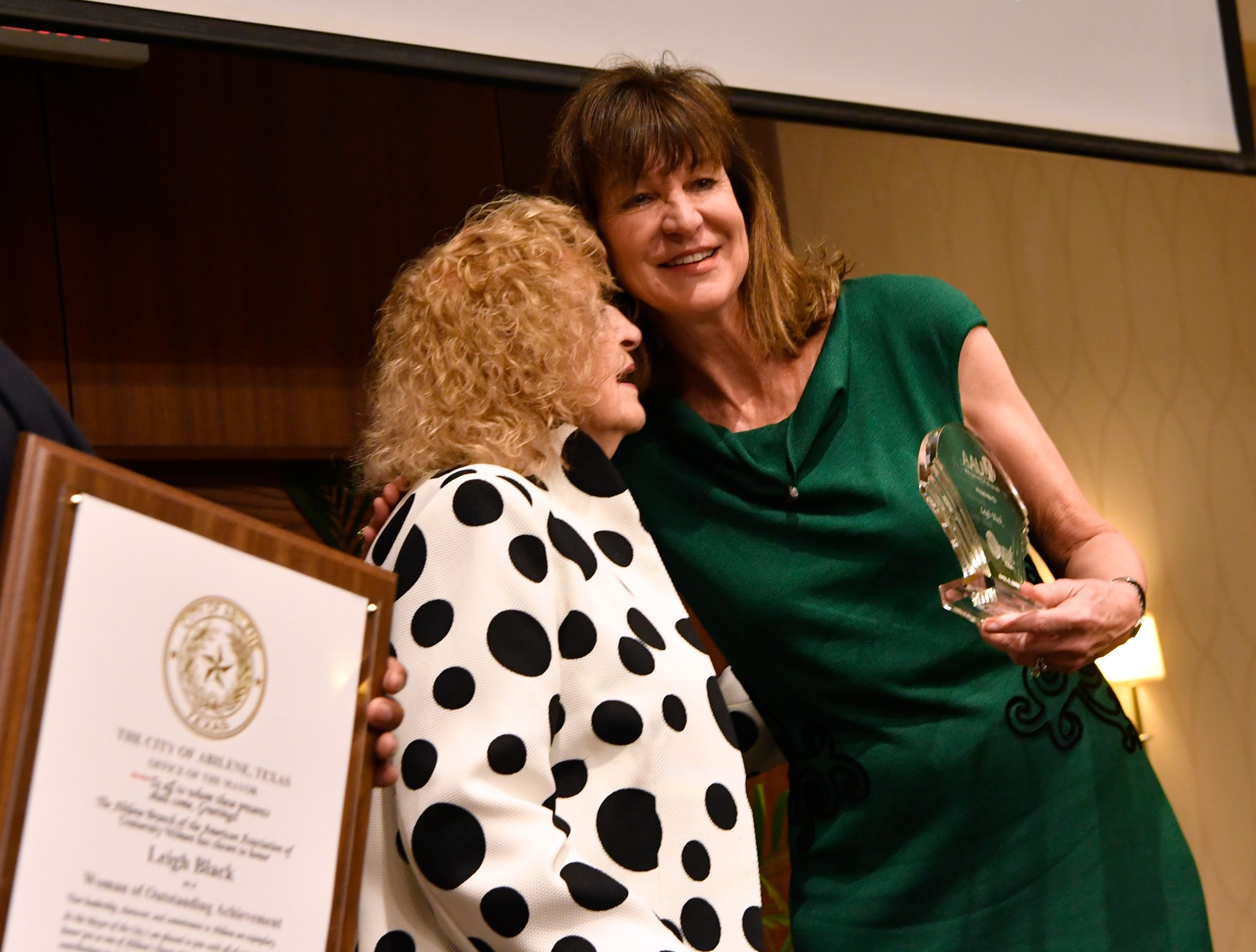 Leigh Black greets Martha Kiel onstage as Abilene Mayor Anthony Williams holds the plaque honoring her at Monday's 10th annual Women of Outstanding Achievement/Women of Promise & Courage Scholarship Award Luncheon at Abilene Christian University.