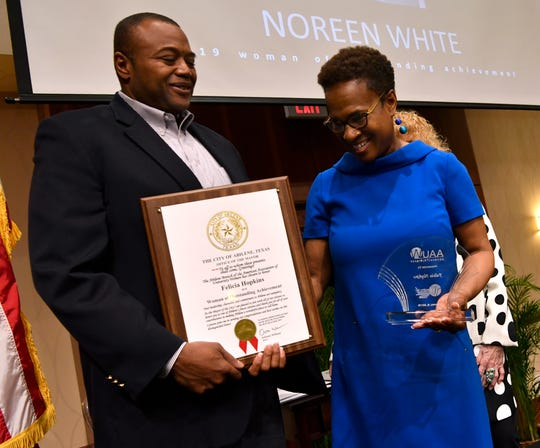 Felicia Hopkins looks at the plaque held by Abilene Mayor Anthony Williams honoring her at Monday's 10th annual Women of Outstanding Achievement/Women of Promise & Courage Scholarship Award Luncheon at Abilene Christian University.