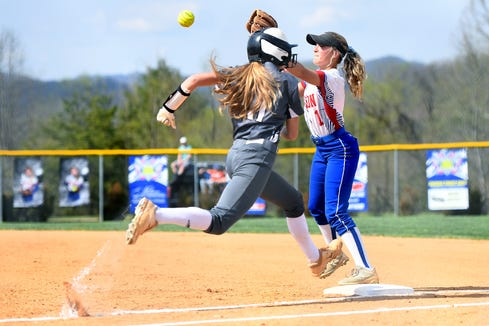 North Buncombe's Scotlyn Eubanks runs for first base as Madison's Bailey Cantrell makes a play during their game at the Andy Gregg softball field in Marshall on April 11, 2019. The Lady Patriots defeated the Lady Blackhawks 6-4.