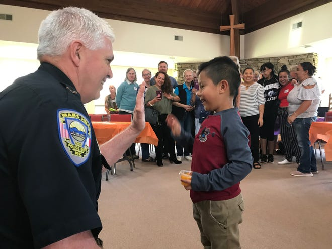 """Mars Hill Police Chief Michael Garrison shares a high-five with a young child at the """"Lunch with the Law"""" event April 11."""