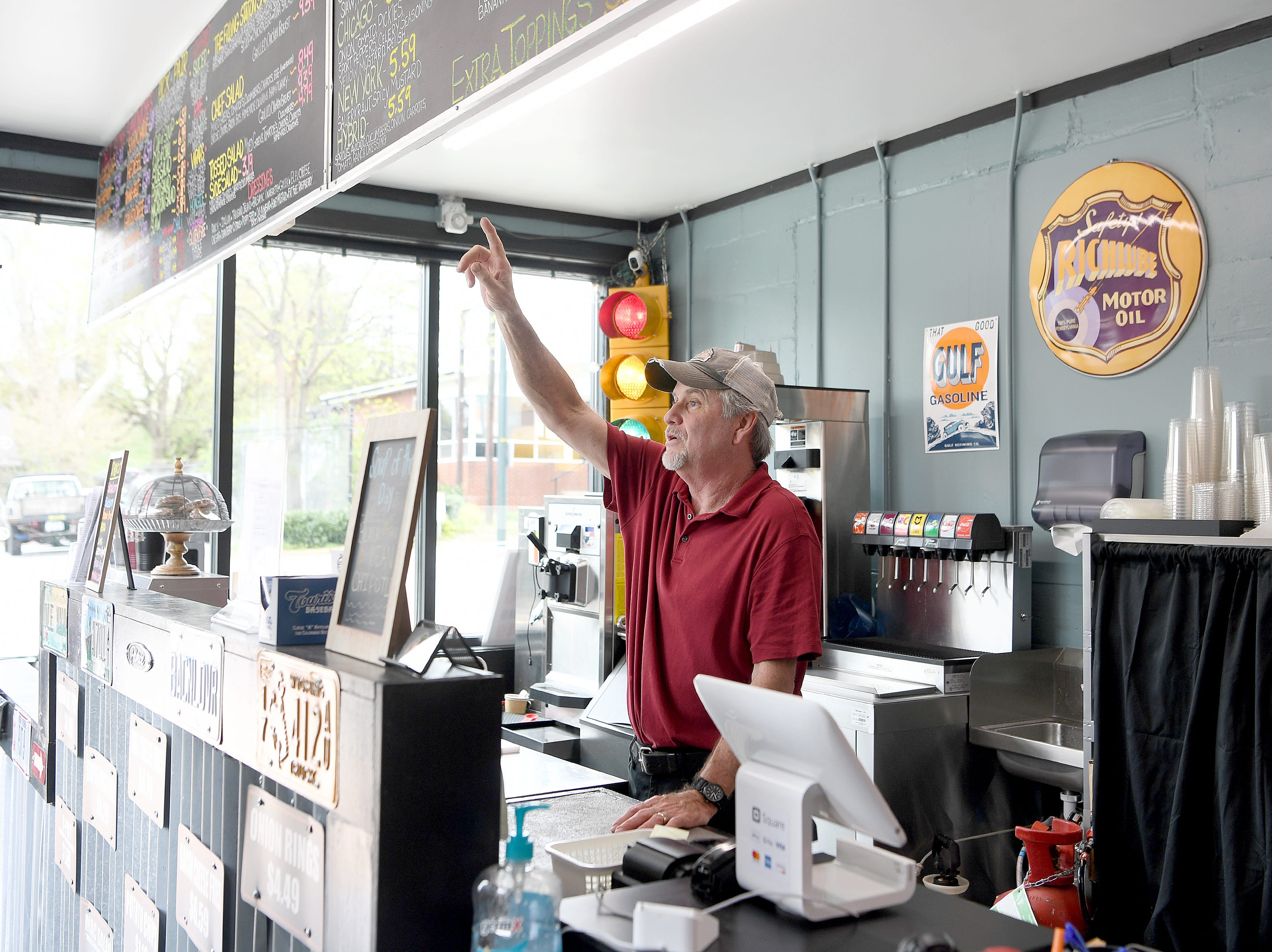 """Barry Tetrault, owner of High Test Deli and Sweet Shop, gives a """"tour"""" of the menu to a customer at his Asheville South Slope location on April 12, 2019."""