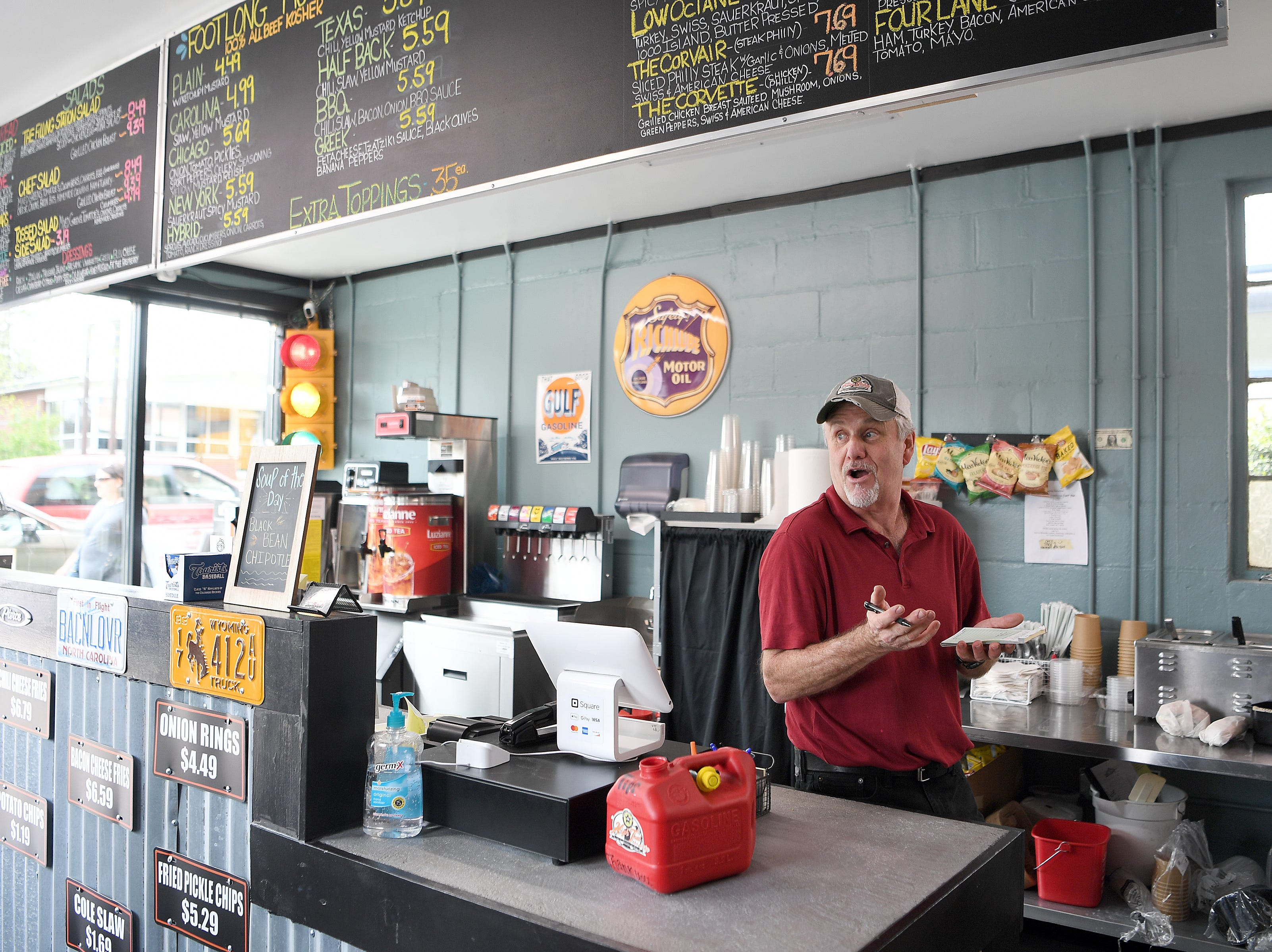 Barry Tetrault, owner of High Test Deli and Sweet Shop, takes a customer's order at his Asheville South Slope location on April 12, 2019.