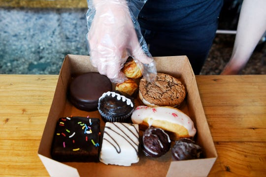 Susie Pearson, owner of Sunshine Sammies, places an assortment of desserts in a box April 4, 2019.