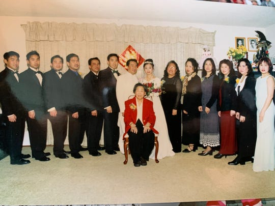 Hau Tat (front, seated) with 13 of her children, plus a new in-law as part of a wedding in this undated photo.