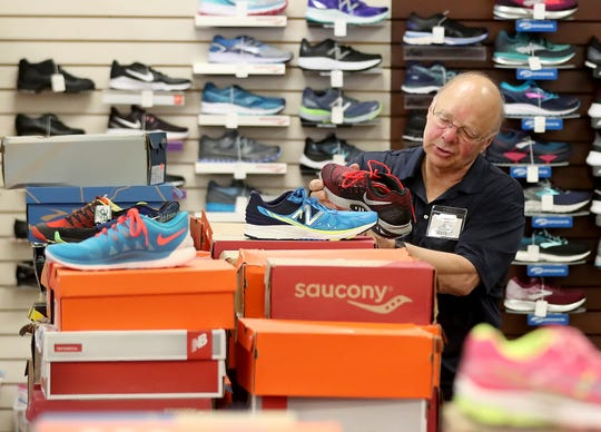 Ed Huisingh helps a customer pick out the right shoes at Sport Haus in Poulsbo on Thursday, April 11, 2019. After 35 years owners Ed and Paulette Huisingh are closing the store to retire.