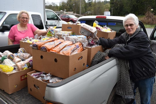 From left, North Mason Food Bank Director Linda Rogers and volunteer Ginnie Nelson accept a donation of bread from the Franz outlet store. The North Mason Food Bank is expanding hours and looking ahead to make building improvements to its site in Belfair.