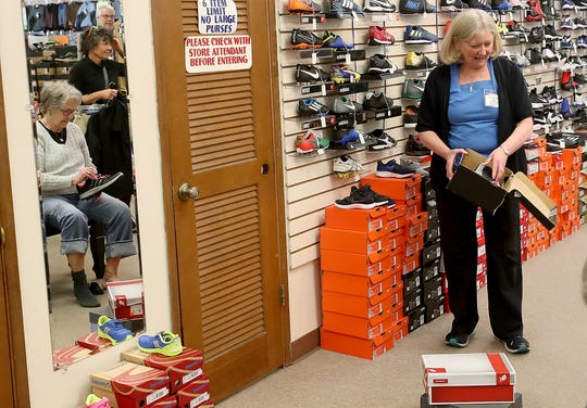 Paulette Huisingh helps a customer find the right size of shoes at Sport Haus in Poulsbo on Thursday, April 11, 2019. After 35 years Paulette and husband Ed are closing the store and retiring.