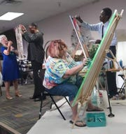 Artist Joan Crutcher, seated, works on a painting during a service at Unity of Melbourne.