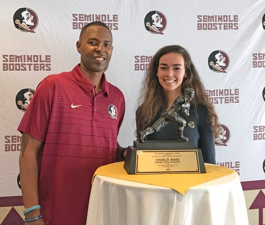 Holy Trinity student newspaper Sports Editor Julia McCarthy has her picture taken with 1993 Heisman Trophy winner Charlie Ward, who was the Brevard Seminole Club's featured speaker at Suntree Country Club on Thursday night.