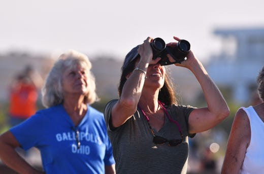"Lucy Graziano watches the start with binoculars. The people on the beach at the north end of Cape Canaveral got a great view of the take-off and landing of SpaceX Heavy launched by Launch Pad 39A at the Kennedy Space Center on Thursday night at 18:35. The rocket carried the communications satellite Arabsat 6A. The auxiliary amplifiers landed at the Cape Canaveral Air Force Station and the core booster landed on the course ""Of course I'm still alive"" & # x9D; Drone ship"