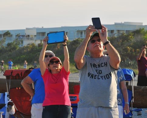 "Philomena Link and Ed Valenti take the start with their tablet and mobile phone. The people on the beach at the north end of Cape Canaveral got a great view of the take-off and landing of SpaceX Heavy launched by Launch Pad 39A at the Kennedy Space Center on Thursday night at 18:35. The rocket carried the communications satellite Arabsat 6A. The auxiliary amplifiers landed at the Cape Canaveral Air Force Station and the core booster landed on the course ""Of course I'm still alive"" & # x9D; Drone ship"