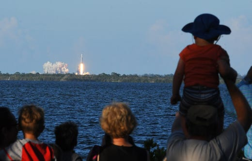 The SpaceX Falcon Heavy takes off from Kennedy Space Center Pad 39A, seen from Nicol Park, Port St. John, along the shoreline of the Indian River in Brevard County.