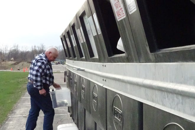 A man sorts recyclables into a trailer while volunteering at the Crawford County Recycling Center drop-off site at Galion schools last year.