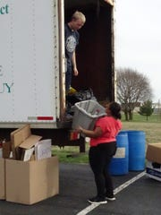 Ashanea Mills, a Galion High School sophomore, hands a bin full of recyclables up to junior Andrew Jones as the two volunteer at the Crawford County Recycling Center drop-off site in Galion on Thursday.