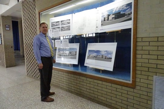 Wynford Superintendent Fred Fox stands in front of a display of plans for the district's new building for the junior high and high schools.
