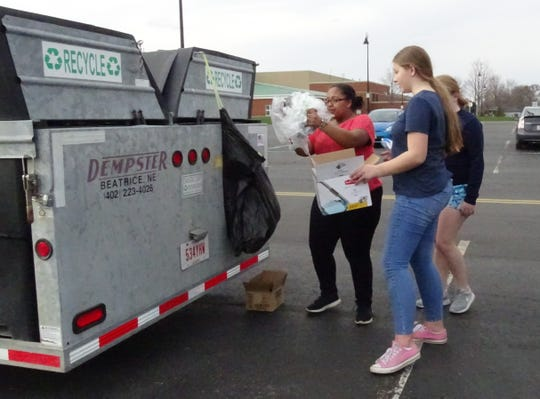 Ashanea Mills and Hannah Daniels sort recyclables while volunteering at the Crawford County Recycling Center drop-off site at Galion schools on Thursday.
