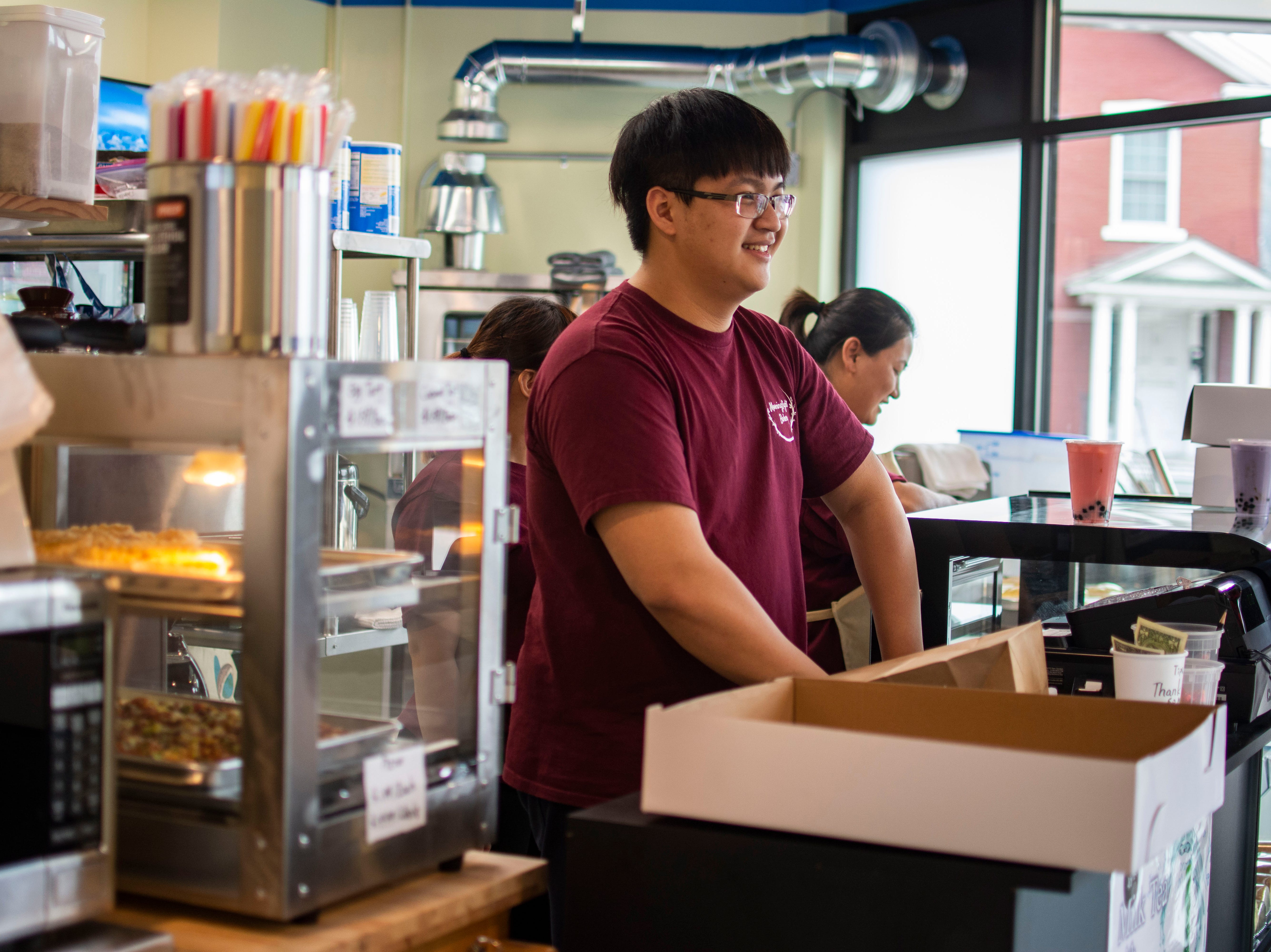 Ken Liu, a UVM computer science student, works the counter at his parents' Morning Light bakery on April 12, 2019