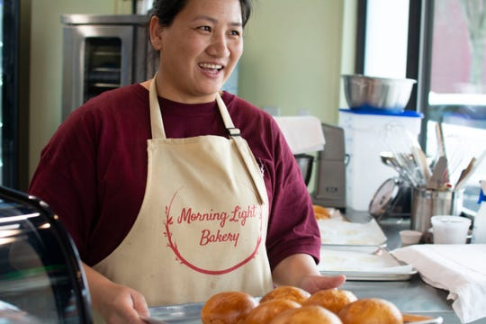 Lai Na Wong learned to bake in Hong Kong. She pulls fresh buns out of the oven on April 12, 2019, one day after fulfilling her dream by opening a bakery in Winooski