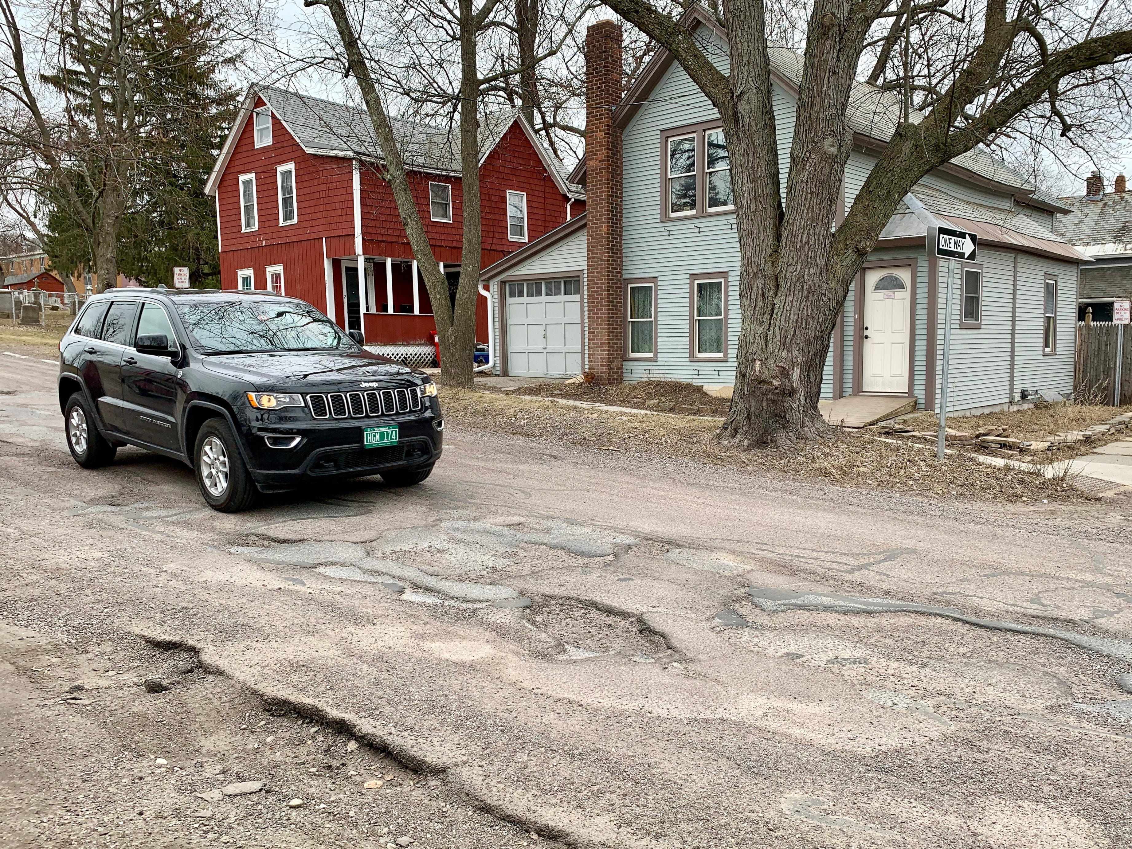 "A Jeep navigates between potholes and worn, ""delaminated"" pavement on Archibald Street in Burlington on Friday, April 12, 2019."