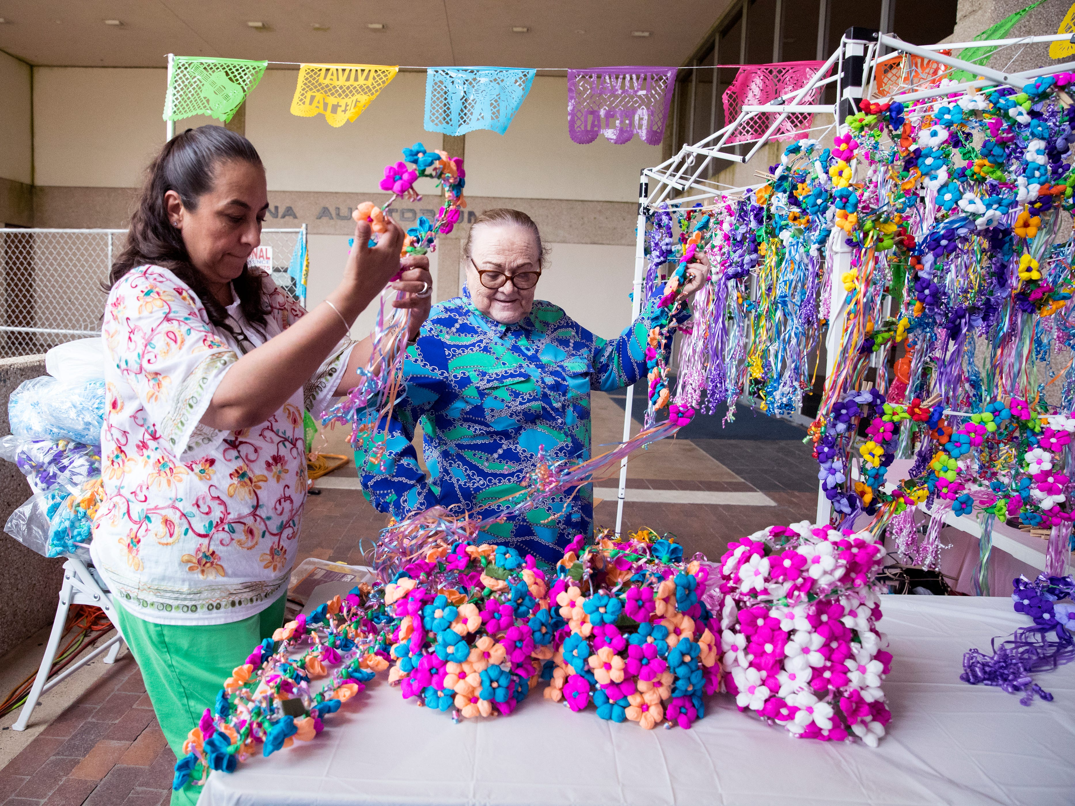 Lorena Rodriguez (left) and Elena Marie sets up their booth in The Mercado in the American Bank Center before Fiesta de la Flor opens on Friday, April 12, 2019. The festival is in honor of the late Tejano singer Selena Quintanilla-Perez. The two-day music event is held in Corpus Christi, Texas.
