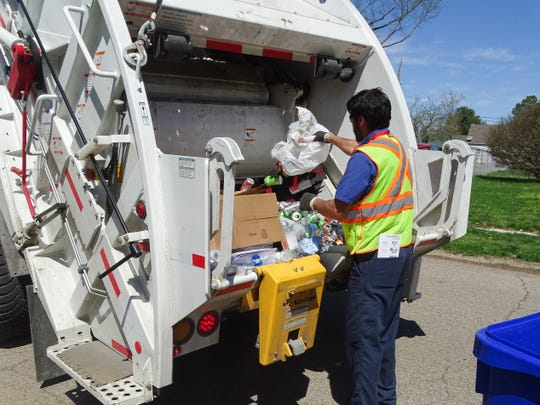 Ryan Owen empties a bag of cans into the truck. Residents often place their materials in a plastic bag without realizing the bag itself isn't recyclable. Crews then either leave the items or take the time to remove them.