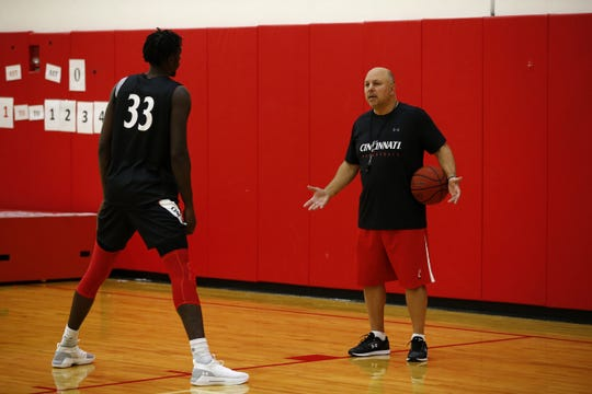 Associate head coach Darren Savino works with junior guard Nysier Brooks during the University of Cincinnati basketball media day in the practice gym of the Lindner Center at UC in the University Heights neighborhood of Cincinnati on Monday, Oct. 8, 2018.