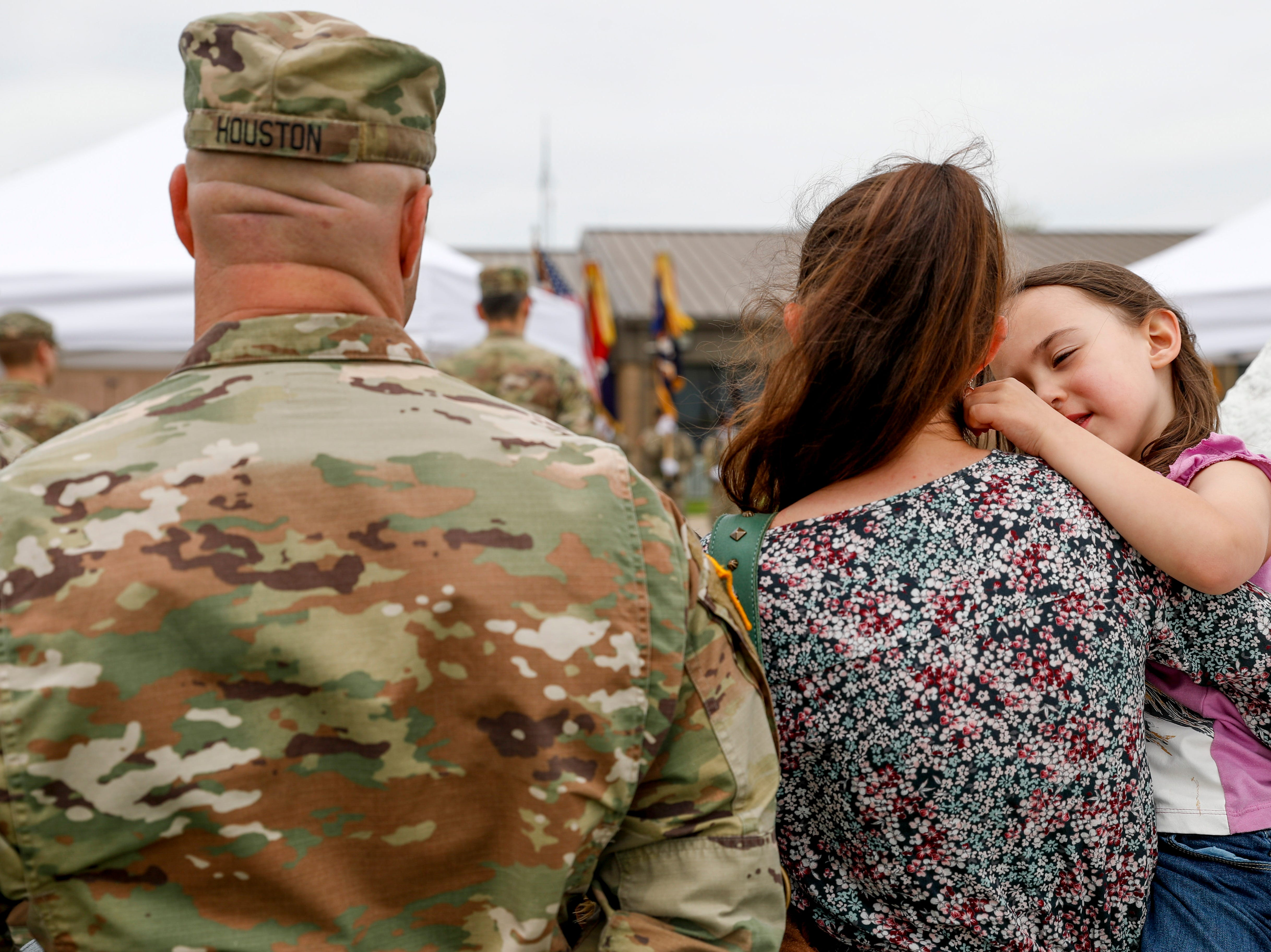 Lylah Houston, 4, right, plays with her mother, Rachel Houston's, hair while watching soldiers with her father 1SG Anthony Houston, left, during a colors casing ceremony prior to deployment for Ukraine at 2 BCT Headquarters in Fort Campbell, KY., on Friday, April 12, 2019.