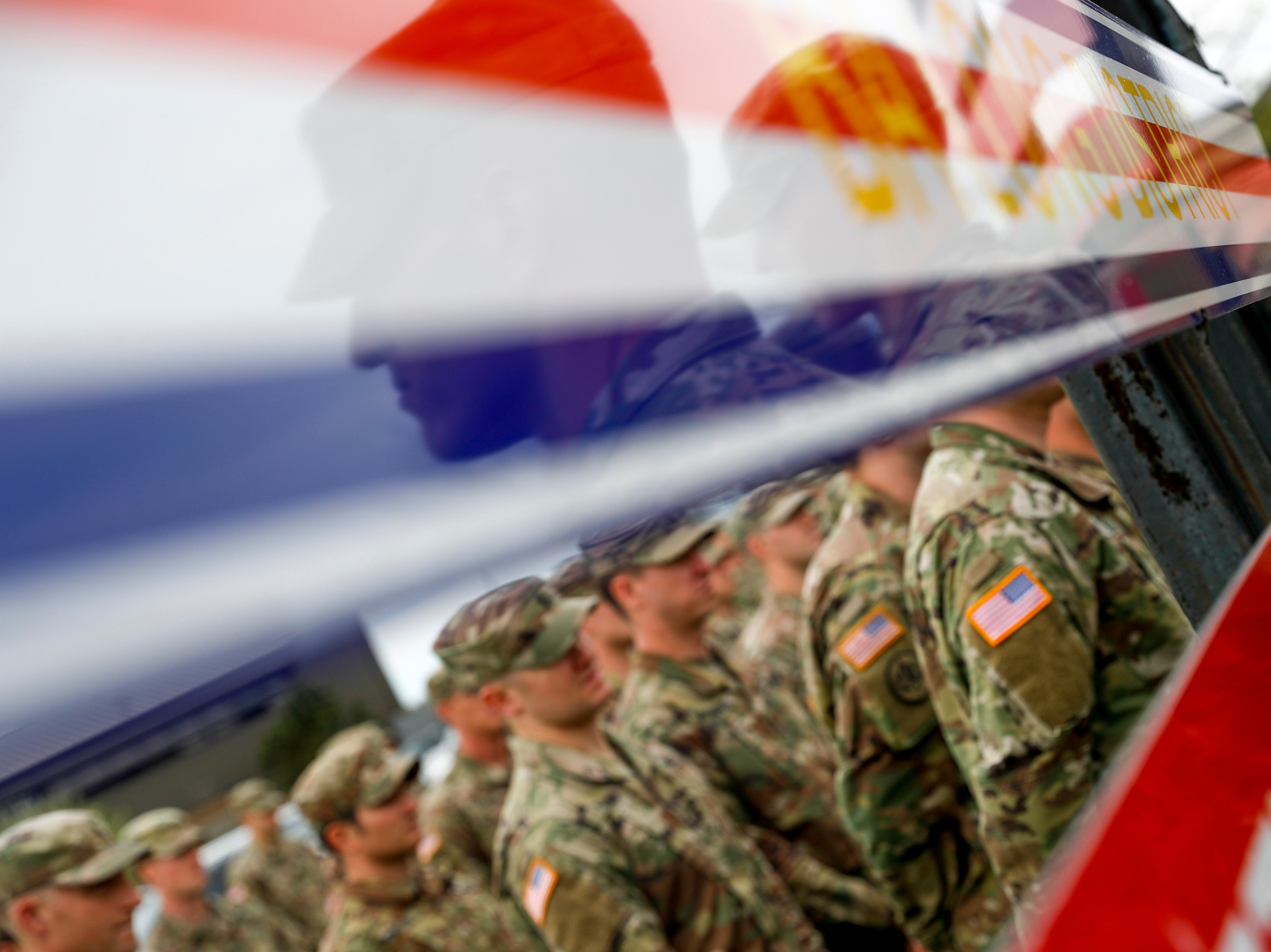 Soldiers stand and watch their fellow soldiers at attention during a colors casing ceremony prior to deployment for Ukraine at 2 BCT Headquarters in Fort Campbell, KY., on Friday, April 12, 2019.