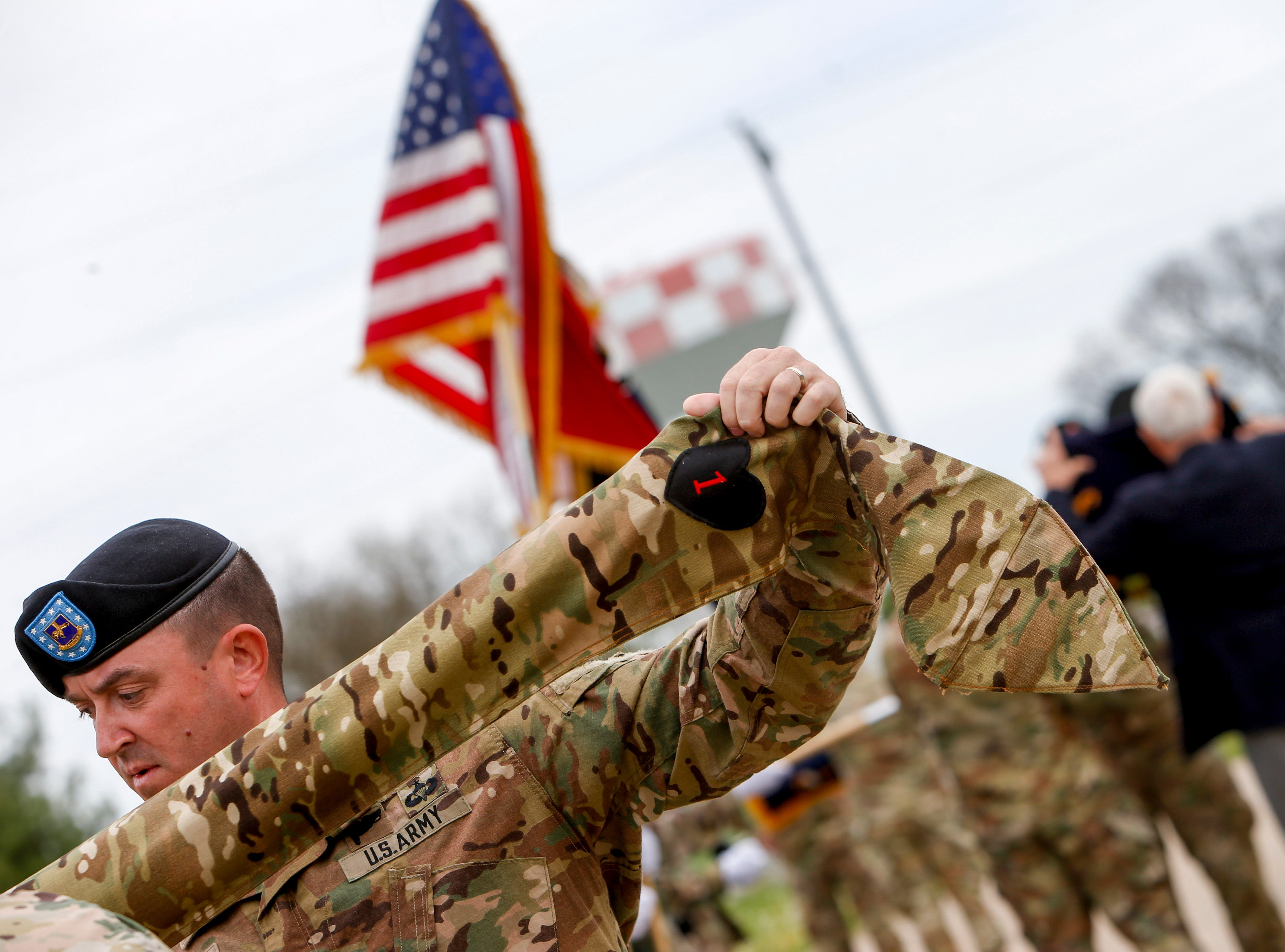 Command Sgt. Maj. Darren Pleskach stretches out the case to guide the guidon in during a colors casing ceremony prior to deployment for Ukraine at 2 BCT Headquarters in Fort Campbell, KY., on Friday, April 12, 2019.