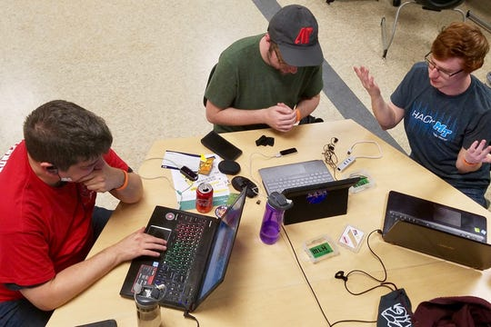 """From the left, Nathan Nickelson, Dylan Engle and Aidan Murphy work on their hack, """"LeapLearning: Sign Language."""""""