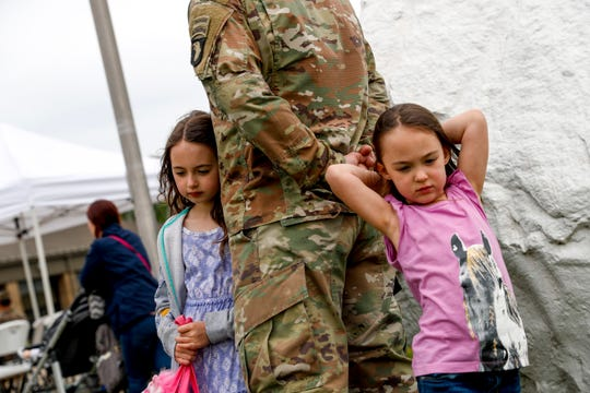 Lylah Houston, 4, left, and Bryleigh Houston, 7, right, lean against their father 1SG Anthony Houston, during a colors casing ceremony prior to deployment for Ukraine at 2 BCT Headquarters in Fort Campbell, KY., on Friday, April 12, 2019.