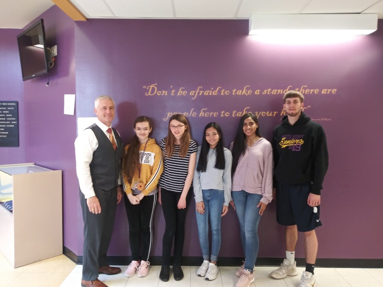 Left to right: Principal - Dr. P. McCabe, and Middle School students: Grade 6 - M. Marcinekova, Grade 7- C. Grace, Grade 8 - D. Bautista  and High School students:  T. Williams and K. Gasiewski.