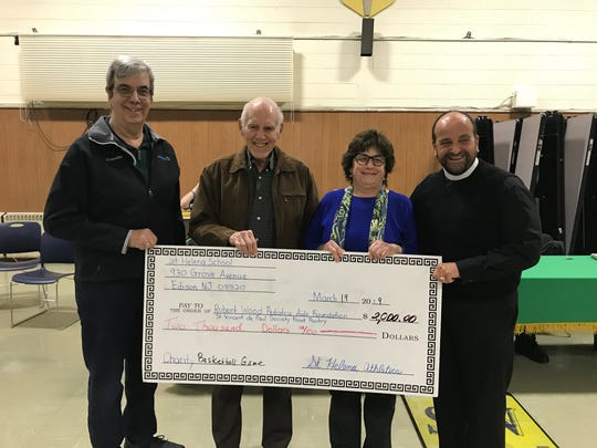 The Perth Amboy St. Vincent dePaul Food Pantry, along with the Robert Wood Johnson Aids Program, were presented with a check from the athletic department of St. Helena's School in Edison. Elena Richards along with Rev Anthony Sirianni coordinated the annual charity basketball games. (Left to right) Jerry Retkwa;Joe Serrao, from the St. Vincent dePaul pantry;Roseann Marone, from RWJ; and the Rev. Anthony Sirrianni, from St. Helena's Church.