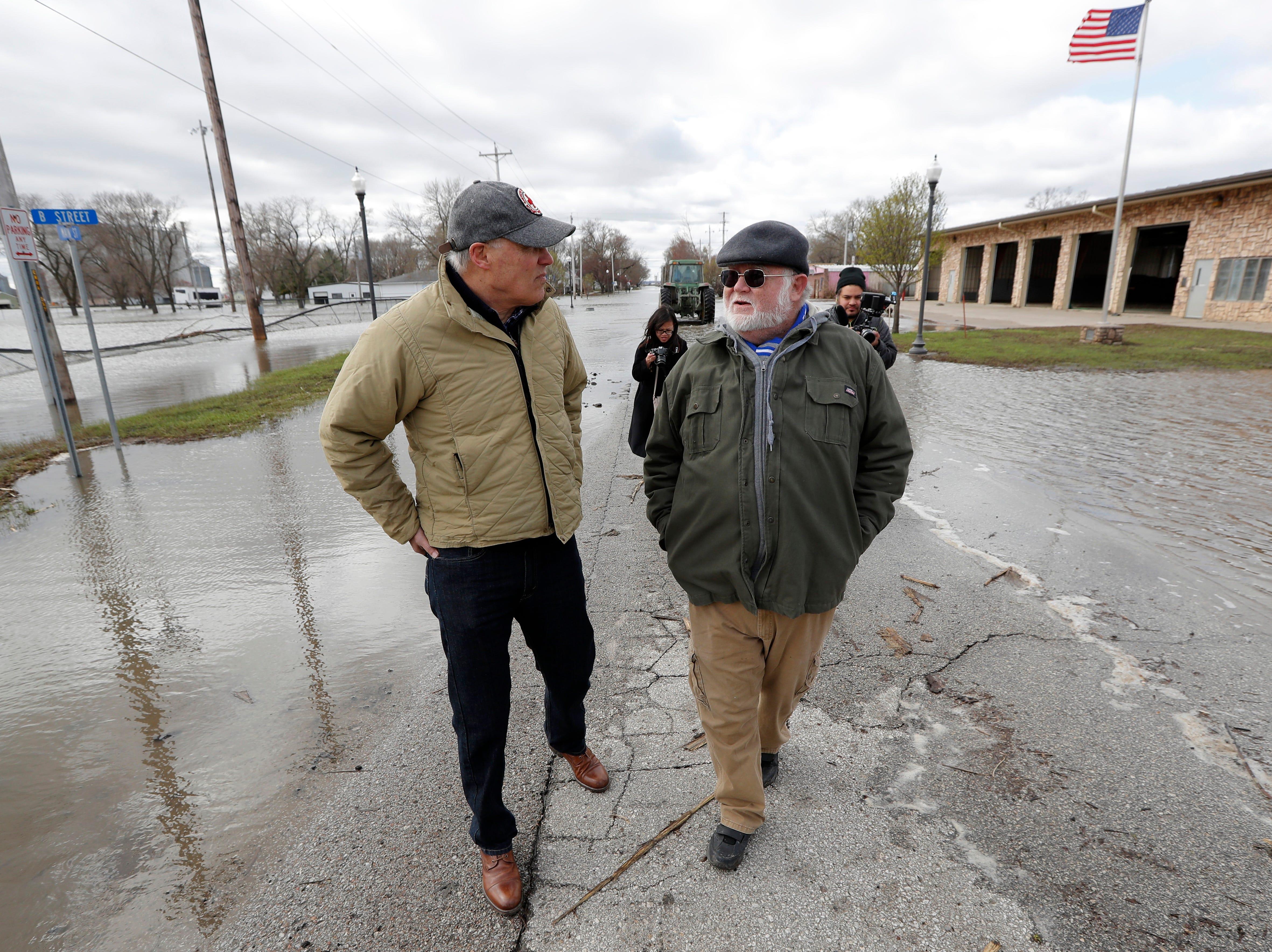 2020 Democratic presidential candidate Washington Gov. Jay Inslee, left, talks with climate analyst John Davis, of Hamburg, Iowa, while touring flood damage, Friday, April 12, 2019, in Hamburg, Iowa.
