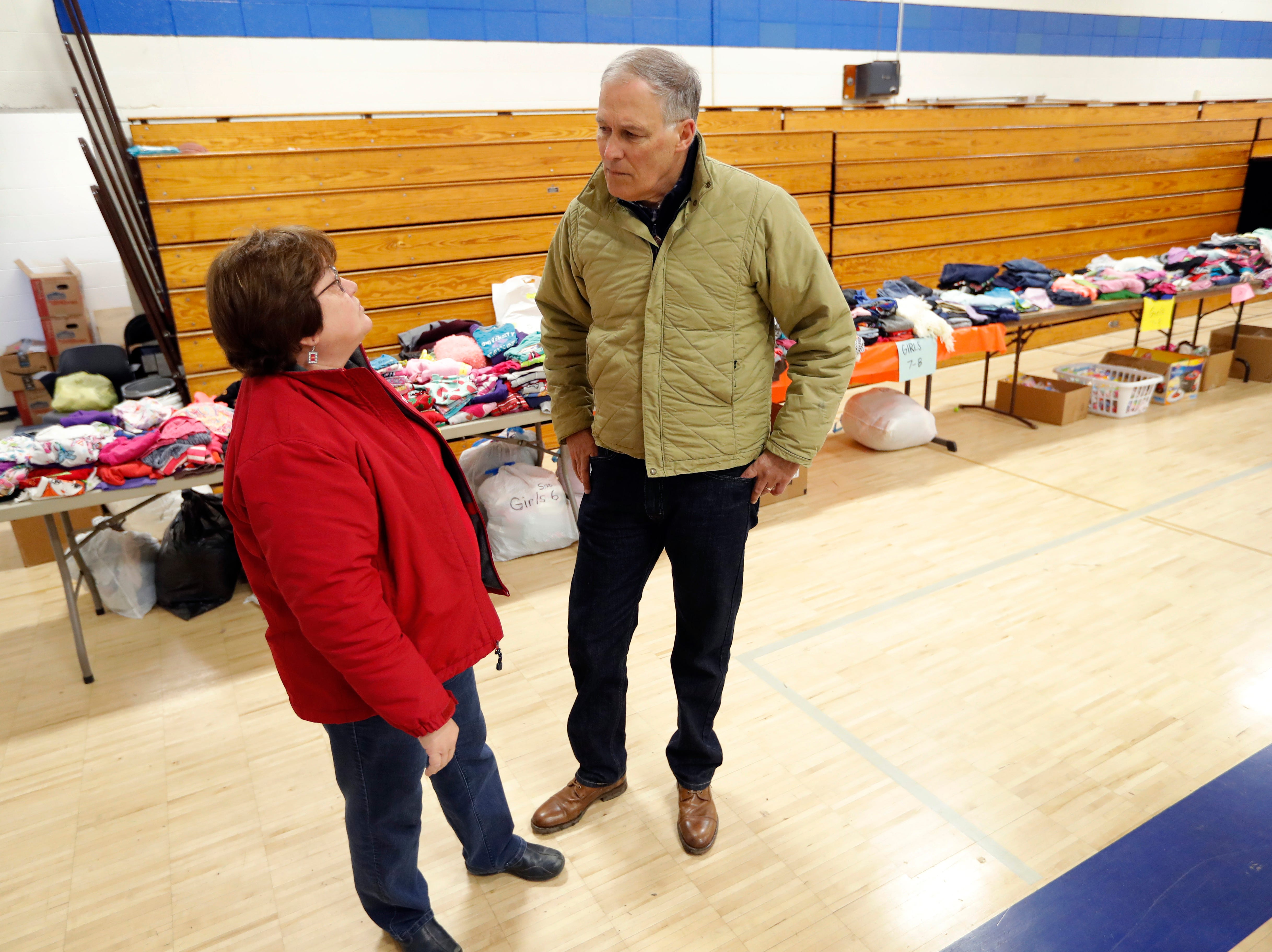 2020 Democratic presidential candidate Washington Gov. Jay Inslee talks with Sandra McKinnon, left, while visiting a flood service support center, Friday, April 12, 2019, in Hamburg, Iowa.