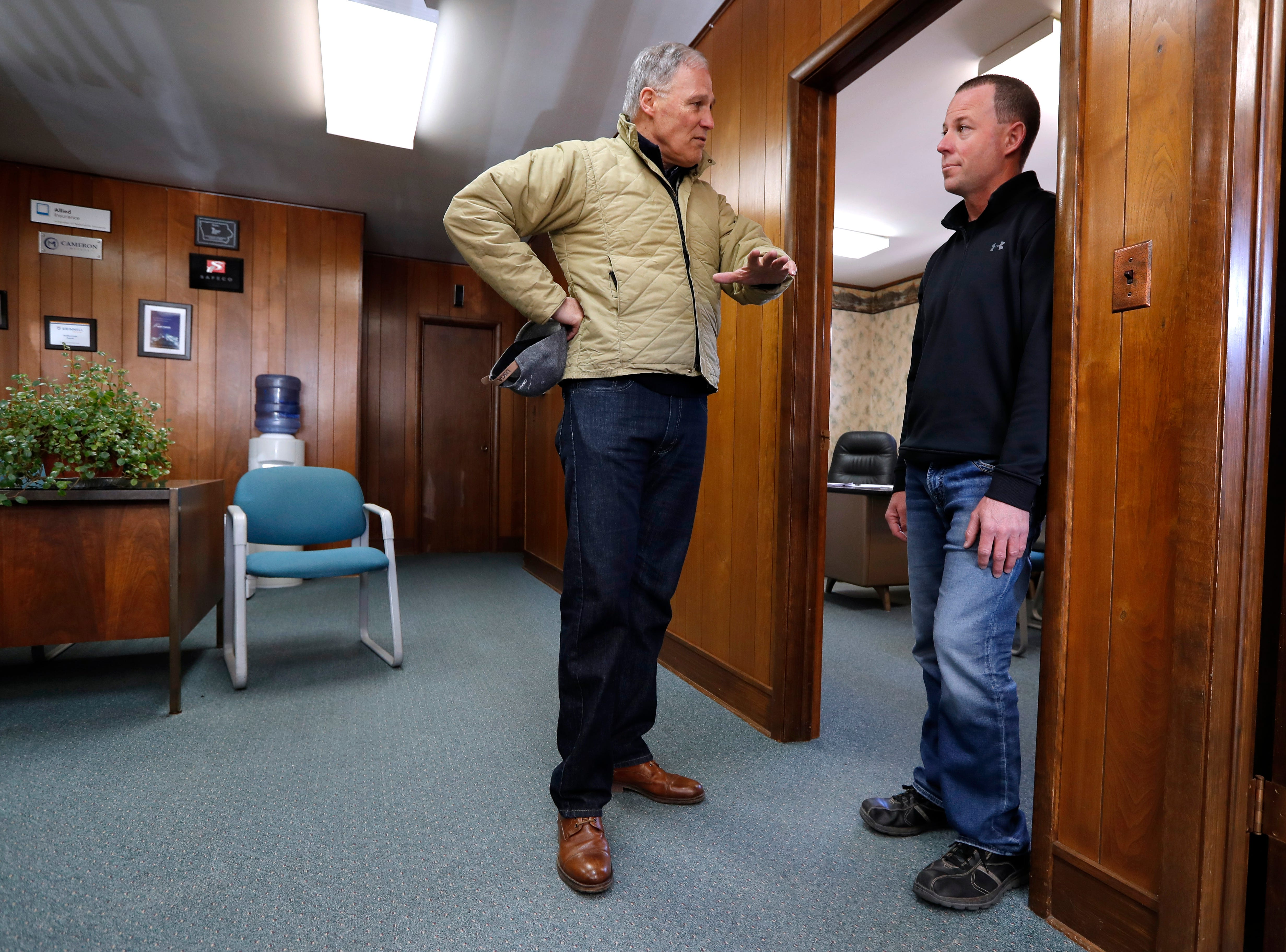 2020 Democratic presidential candidate Washington Gov. Jay Inslee talks with insurance agent Jason Cox, right, while touring flood damage, Friday, April 12, 2019, in Hamburg, Iowa.