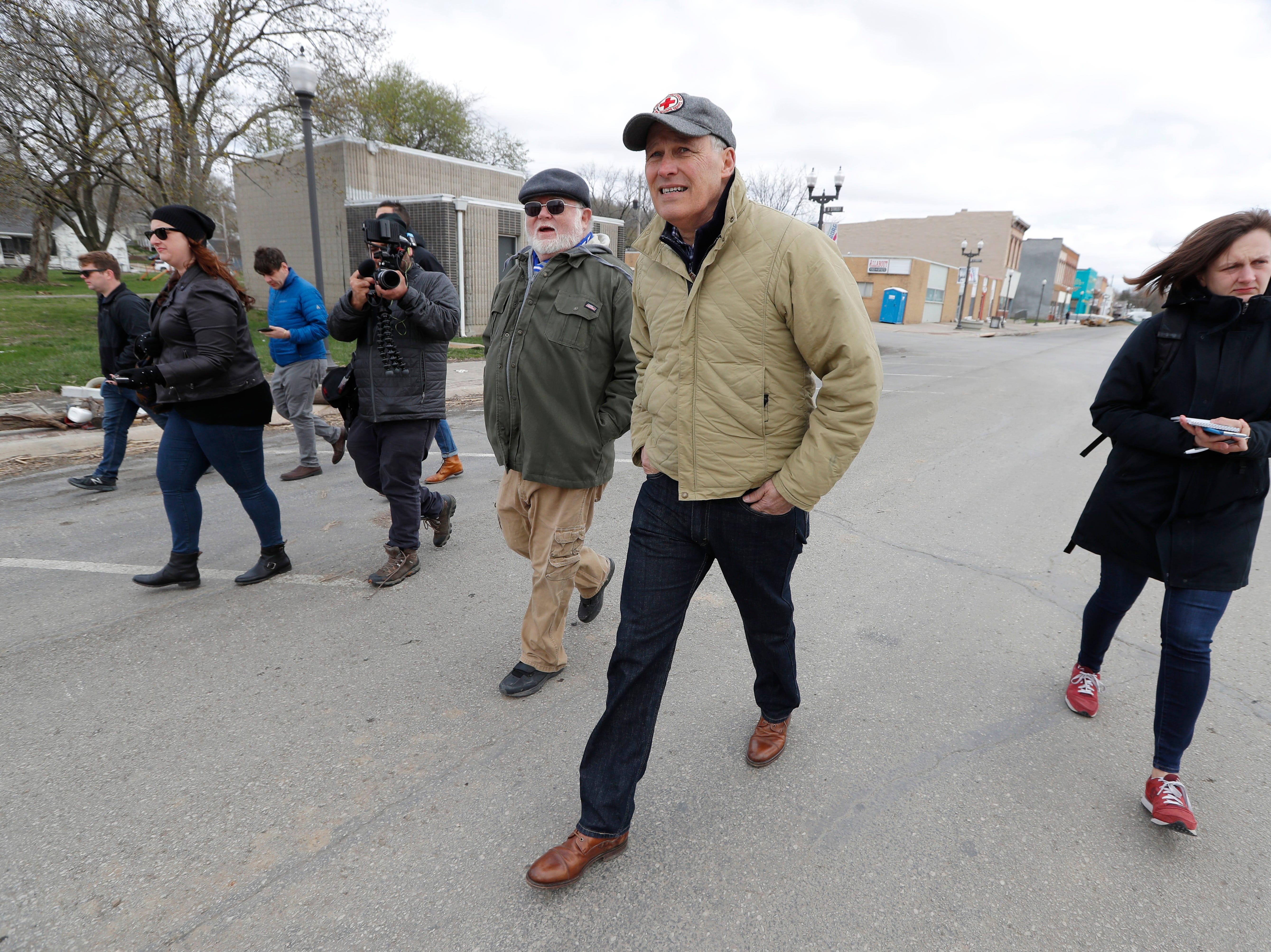 2020 Democratic presidential candidate Washington Gov. Jay Inslee, center, tours flood damage, Friday, April 12, 2019, in Hamburg, Iowa.