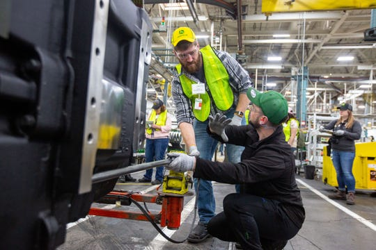 "Travis Van Regenmorter uses a suspended hydraulic tool to at attach a bolt during a ""gold key tour"" at John Deere's Waterloo assembly plant Tuesday, April 9, 2019."